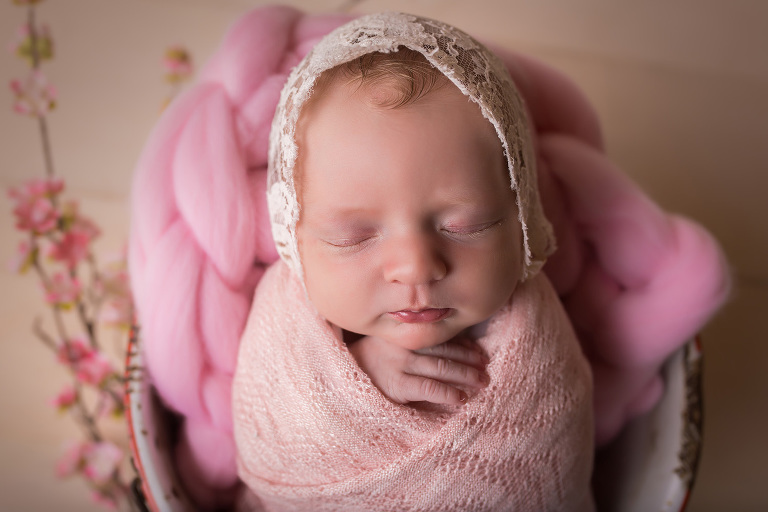newborn photographer in rochester, ny captures newborn baby girl wrapped up in pink with lace bonnet