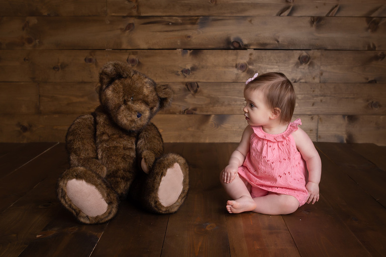family photographer in rochester, ny captures baby girl talking to her teddy bear
