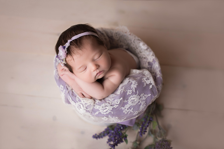 newborn photographer in rochester ny captures baby girl sleeping in a bucket with her chin on her hands