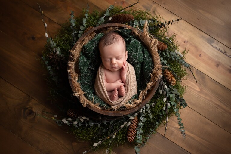 newborn photographer in rochester ny captures newborn baby boy sleeping in a rustic pine wreath