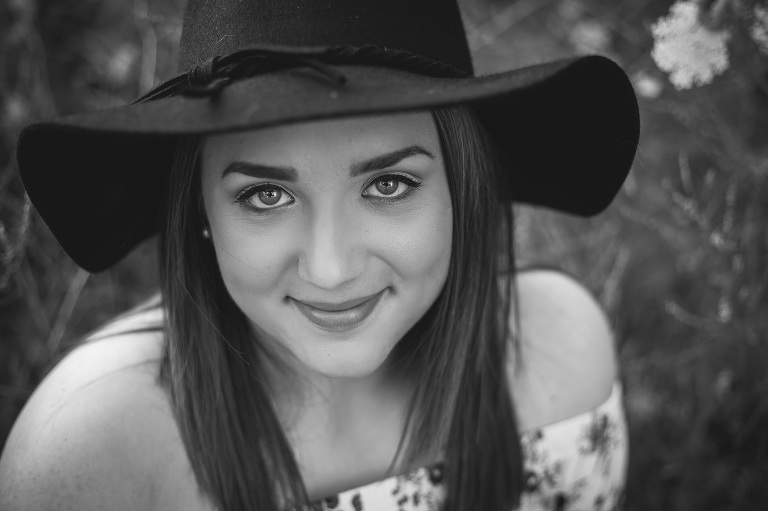 family photographer in rochester, ny captures senior girl wearing hat and smiling
