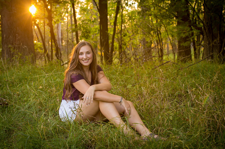 family photographer in rochester, ny captures senior girl smiling as the sun sets behind her