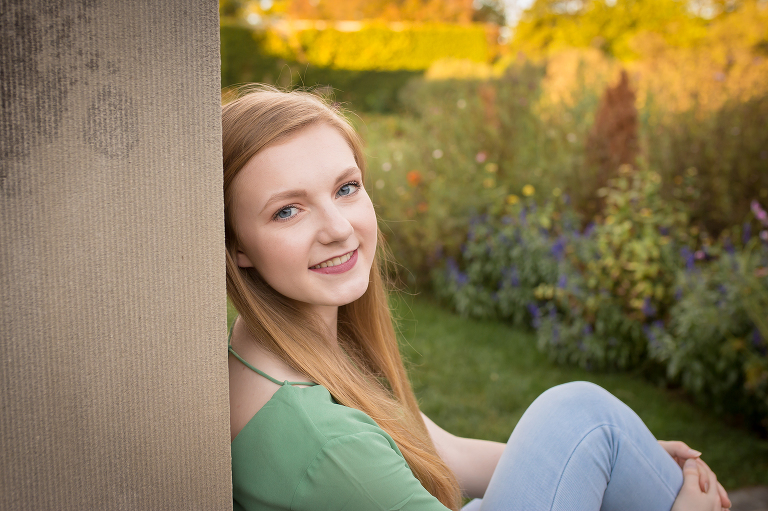 rochester, ny photographer captures highschool senior smiling in the gardens at the George Eastman Musuem