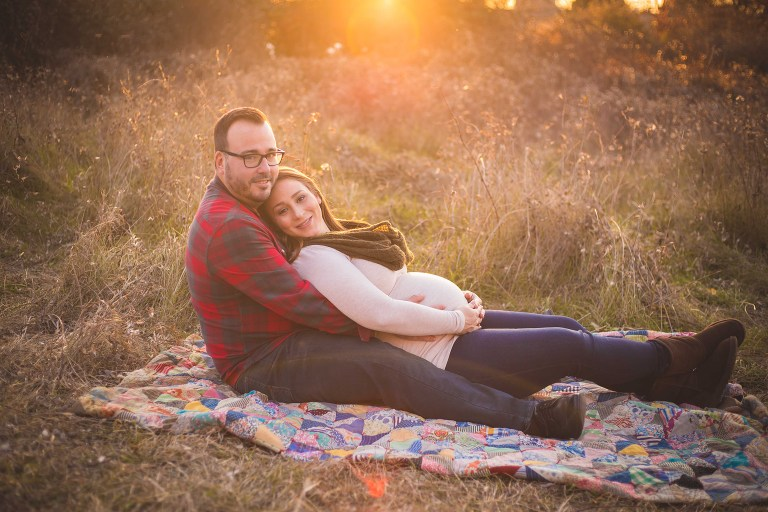 maternity photographer in rochester ny captures pregnant mom and dad holding belly