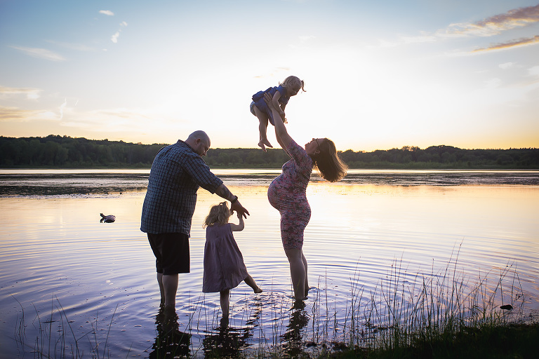 maternity photographer in rochester ny captures family playing in the water at sunset