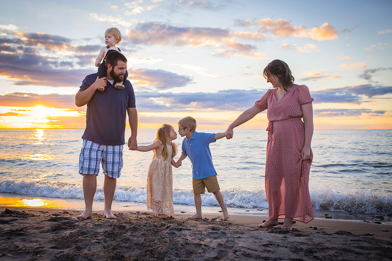 family photographer in rochester ny captures loving family moment on the beach at sunset
