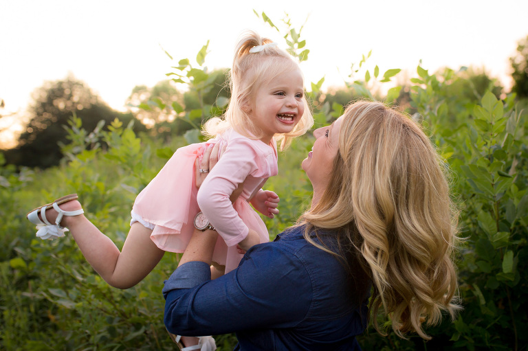 rochester, ny family photographer captures mom throwing little girl in the air