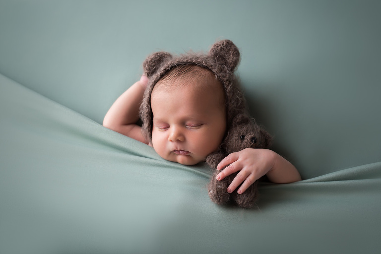newborn photographer in rochester ny baby boy tucked into green blankets with teddy bear and teddy bear bonnet