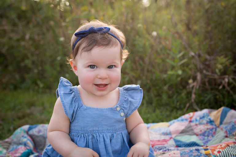 baby photographer in rochester, ny captures little girl in blue dress smiling in a field at sunset