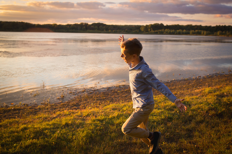 family photographer in rochester, ny captures boy running with arms outstretched into the sunset