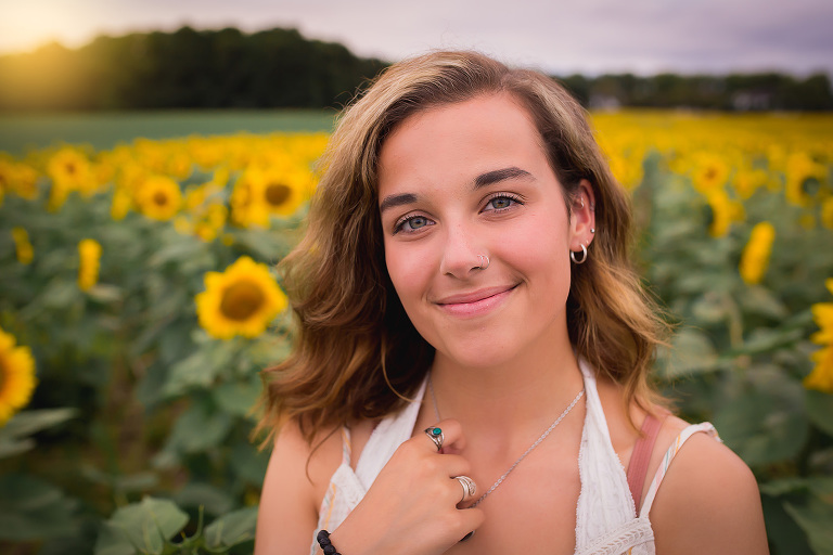 family photographer in rochester, ny captures highschool senior smiling in a field of sunflowers at sunset