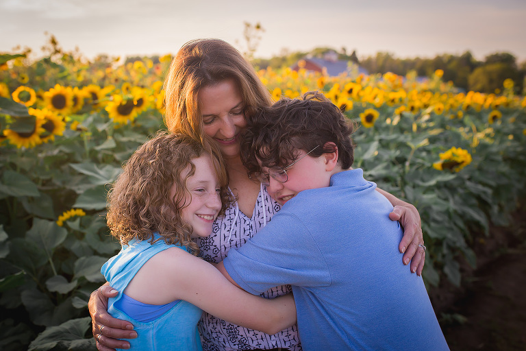 family photographer in rochester ny captures family hugging each other in the sunflowers