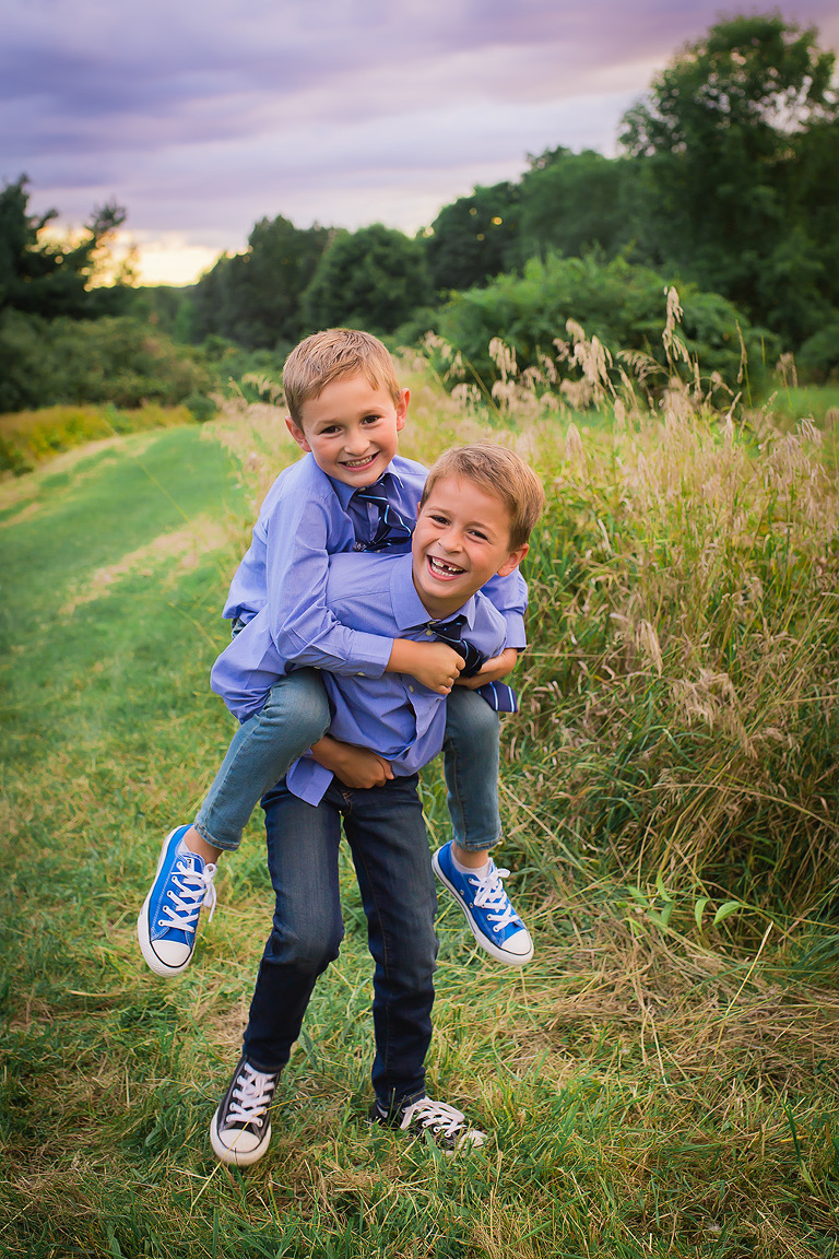 family photographer in rochester, ny captures brothers laughing together in a field