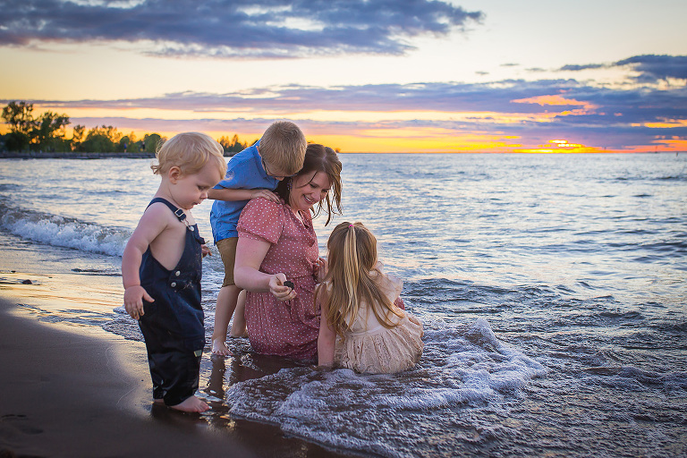 family photographer in rochester ny captures mom playing with her kids in Lake Ontario at sunset