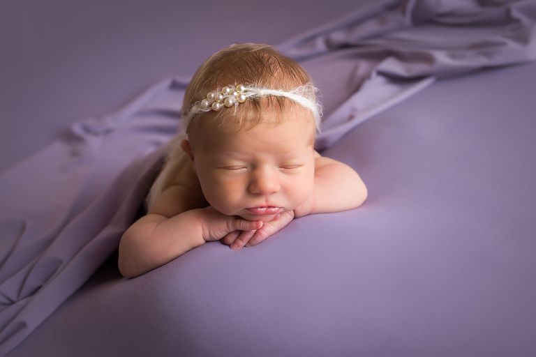 newborn photographer in rochester ny captures baby girl sleeping in purple