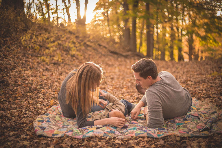 rochester ny family photographer captures family cuddling in the fall leaves
