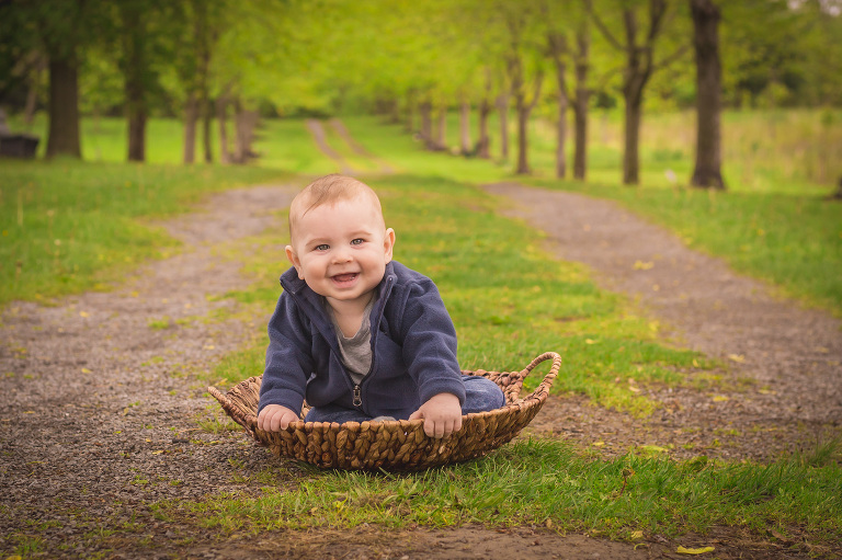 rochester baby photographer captures baby smiling in a basket in a park