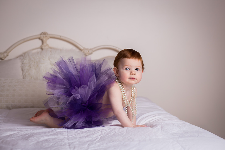 Rochester newborn photographer captures baby in a purple tutu on white bed
