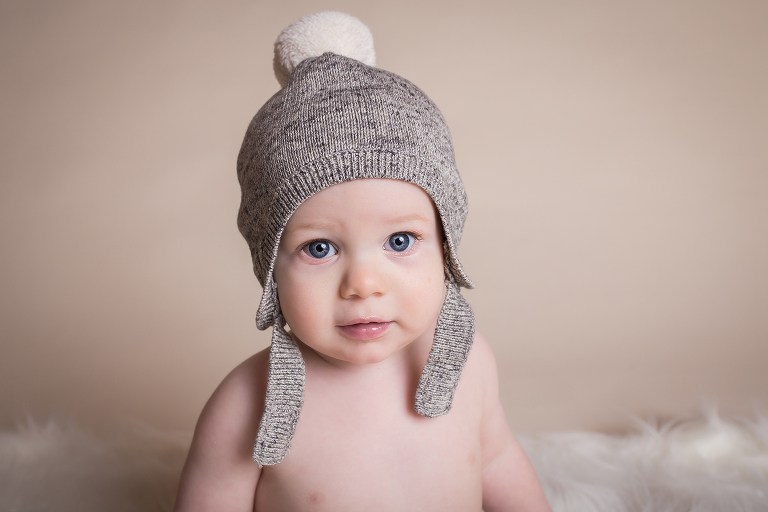 newborn photographer in rochester ny captures baby boy wearing a gray snow hat