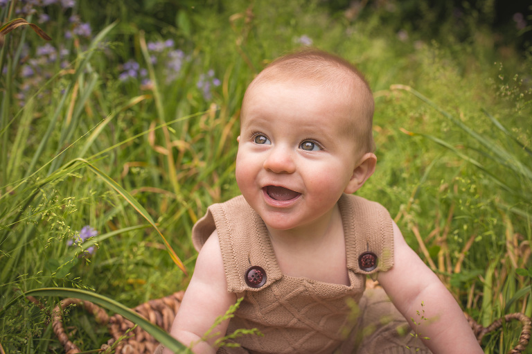 rochester family photographer captures baby wearing knit romper in the tall grasses
