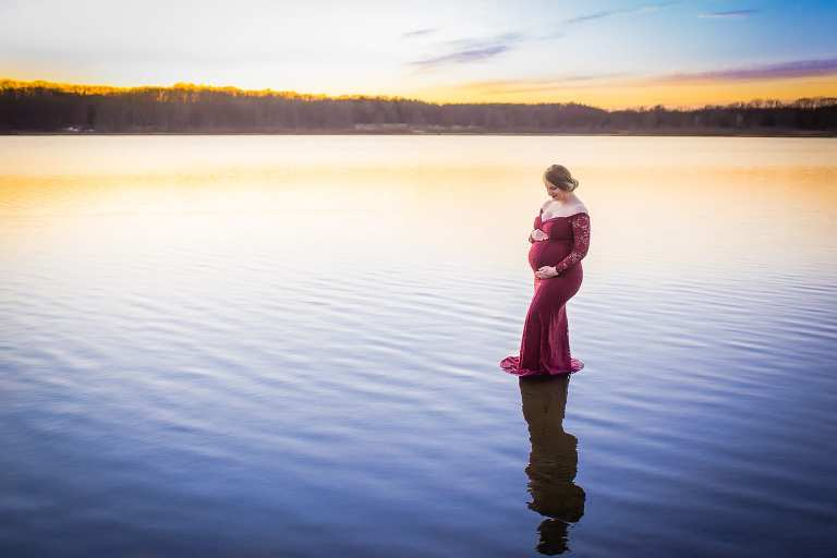 maternity photographer in rochester ny captures mom-to-be holding her belly on the water under the setting sun