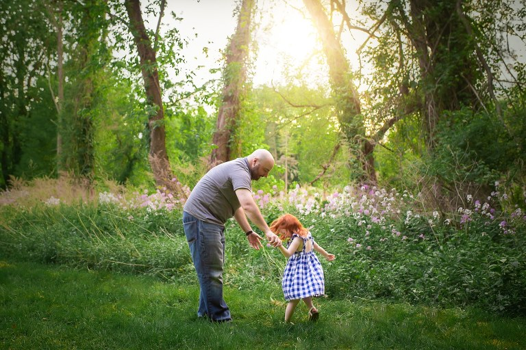 family photographer in rochester ny captures dad and daughter dancing in the sunshine