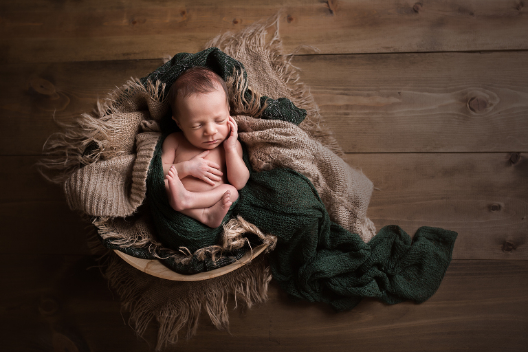 newborn photographer in rochester ny captures baby boy sleeping in a bowl