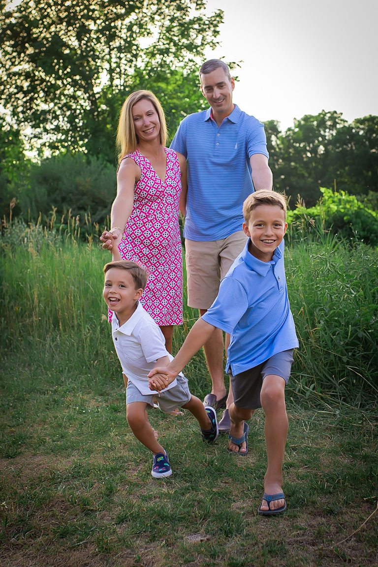 family photographer in rochester ny captures family playing together in the summer sunset