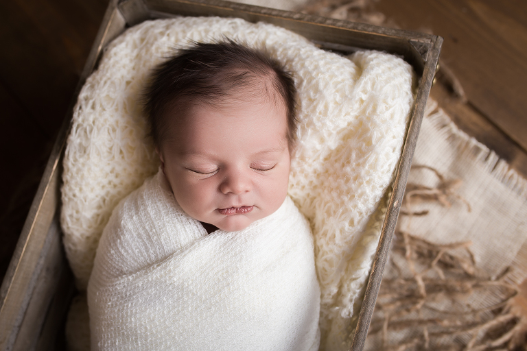 newborn photographer in rochester, ny captures baby sleeping wrapped in white