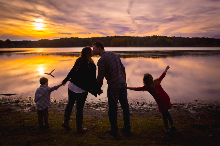 family photographer in rochester ny captures family silhouetted in the sunset over a pond