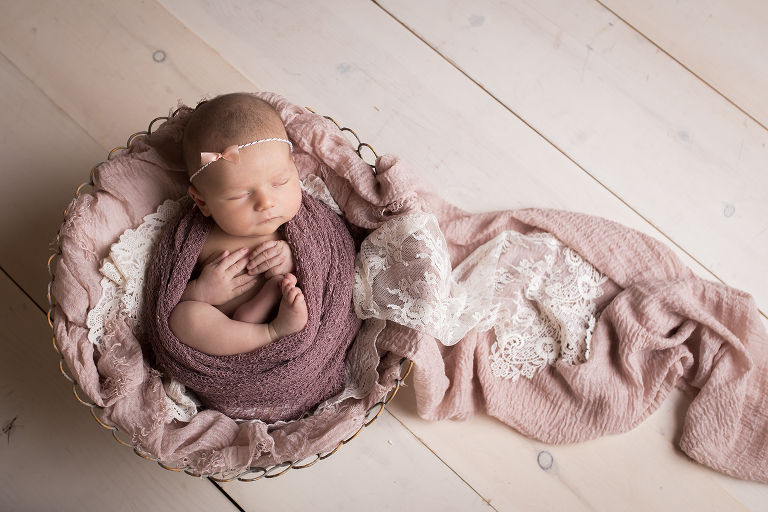 newborn photographer in rochester, ny captures baby girl sleeping in bowl with shades of pink and purple