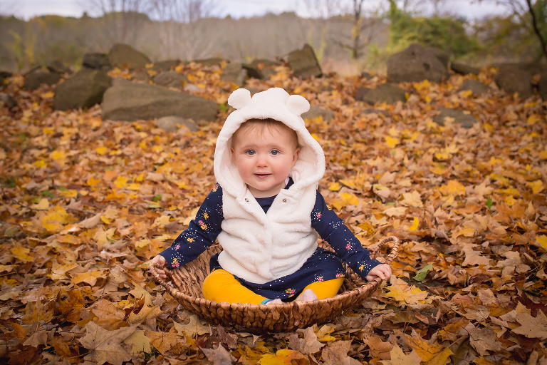 newborn photographer in rochester, ny captures baby girl in teddy bear hoodie in a basket in the fall leaves