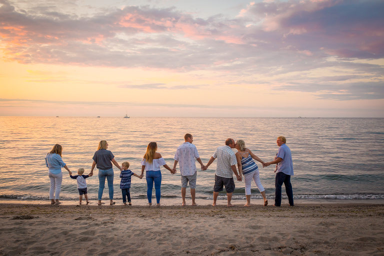 family photographer in rochester ny captures extended family holding hands on the beach at sunset