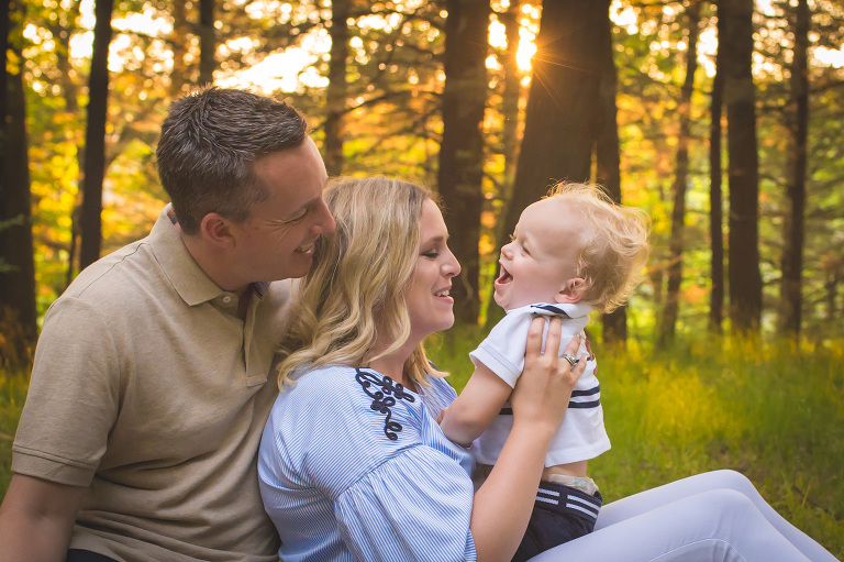 family photographer in rochester ny captures parents playing with toddler in sunset light