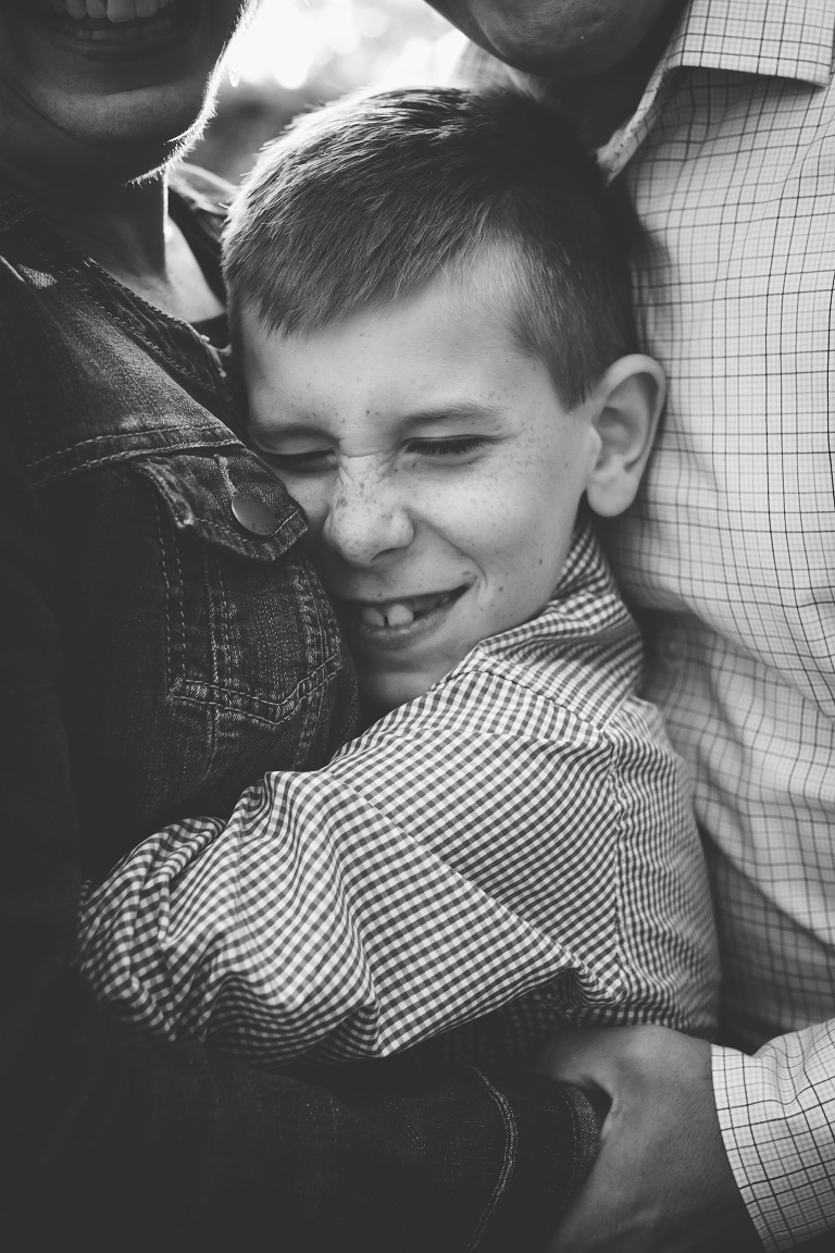 family photographer in rochester ny captures little boy hugging his parents tightly