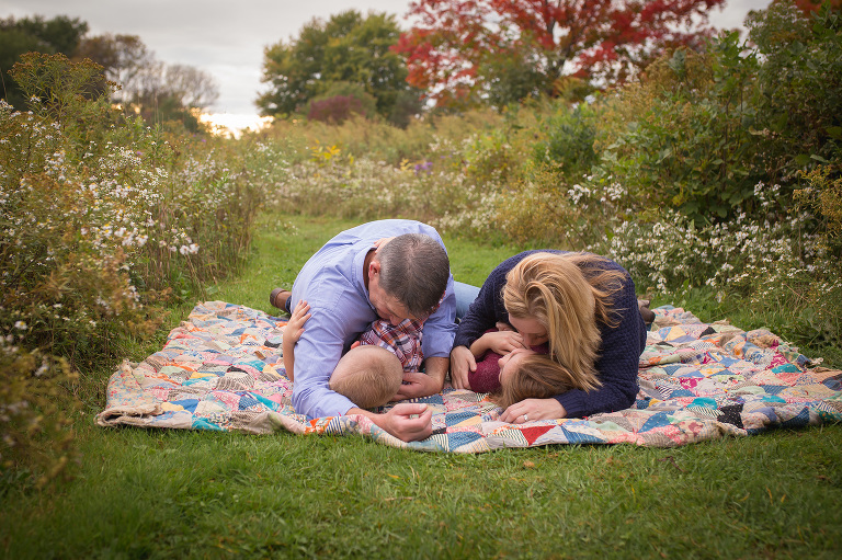 rochester ny family photographer captures family snuggling together in a field