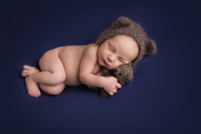 newborn photographer in rochester, ny captures baby boy sleeping in navy blue blankets with teddy bear stuffed animal