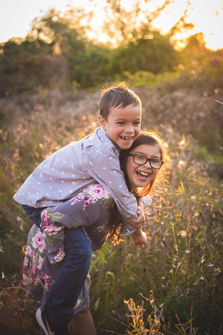 rochester ny family photographer captures sister giving brother a piggy back ride