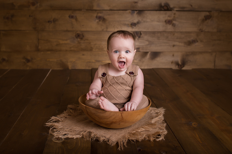 rochester ny newborn photographer captures baby boy sitting in bowl with a huge smile