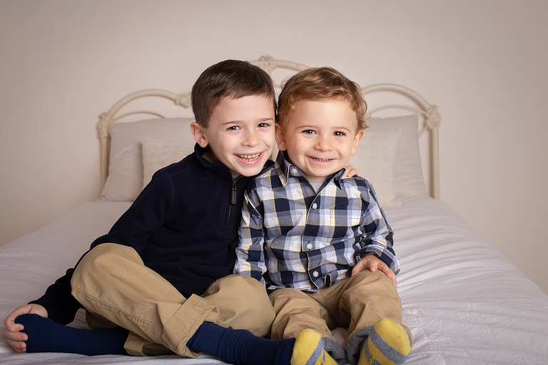 family photographer in rochester ny captures brothers smiling together on a bed