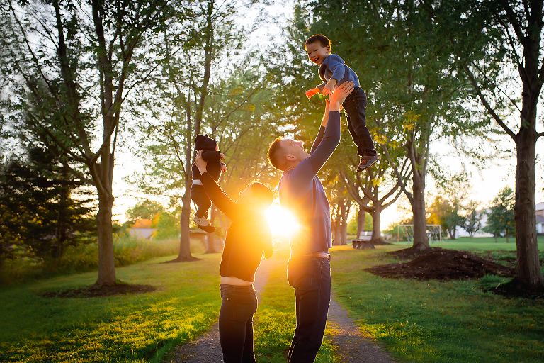 family photographer in rochester ny captures mom and dad lifting up their babies with the sun shining in between them