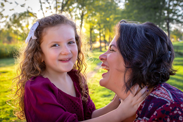 family photographer in rochester ny captures mom and daughter laughing together in the park