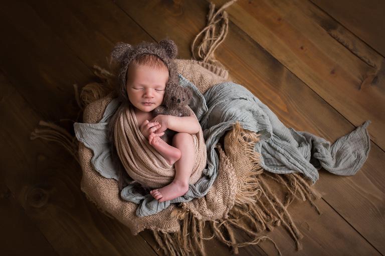 newborn photographer in rochester ny captures baby boy sleeping with teddy bear and teddy bear bonnet
