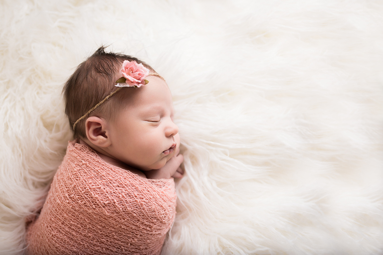 newborn photographer in rochster ny captures baby girl's profile as she sleeps on white fur wrapped in pink blankets