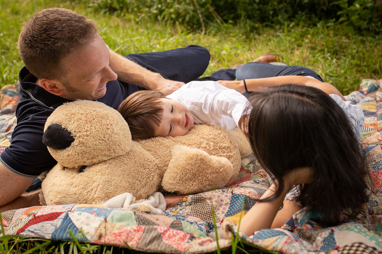family photographer in rochester ny captures family laying on a quilt together cuddling