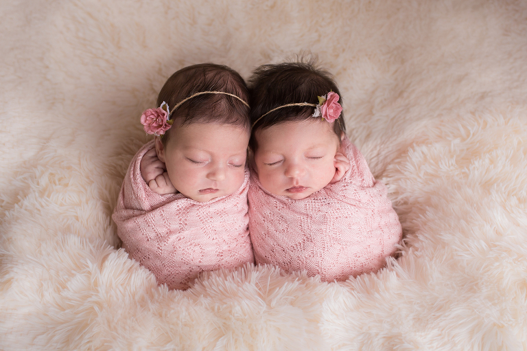 newborn photographer in rochester ny captures twin girls wrapped in pink sleeping together