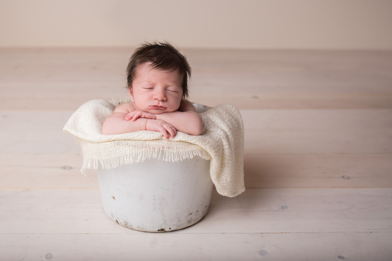 newborn photographer in rochester ny captures baby sleeping in white bucket