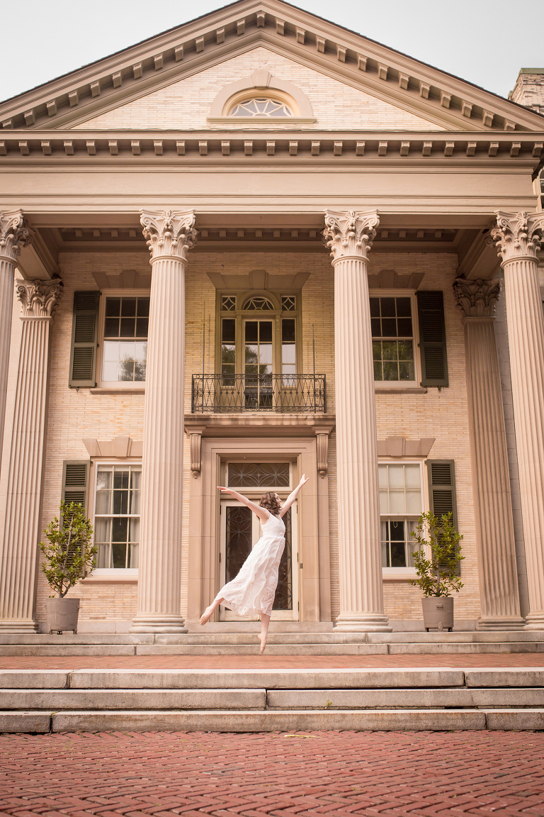family photographer in rochester ny captures high school senior leaping into the air with ballet slippers in front of the george eastman museum