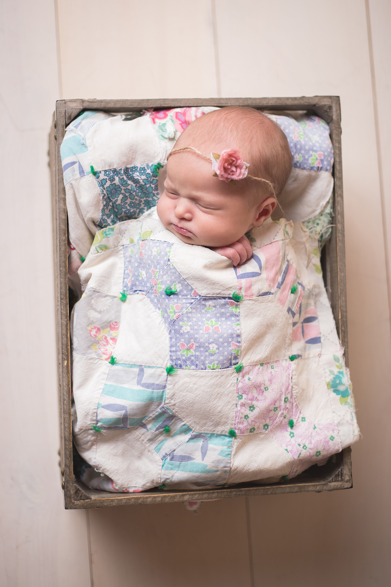 rochester photographer captures newborn baby sleeping in a crate with vintage quilt