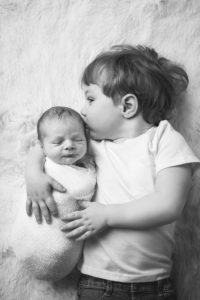 rochester ny child photographer captures toddler kissing baby brother on head